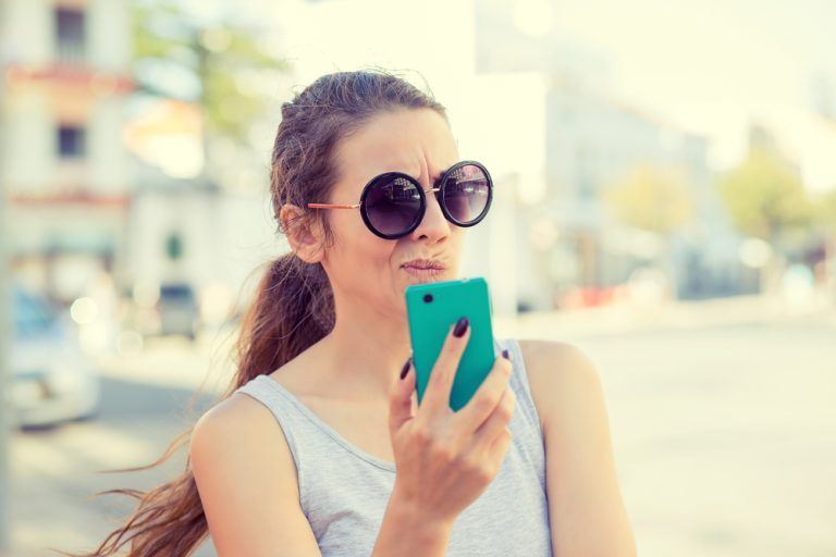 woman having trouble reading her mobile phone